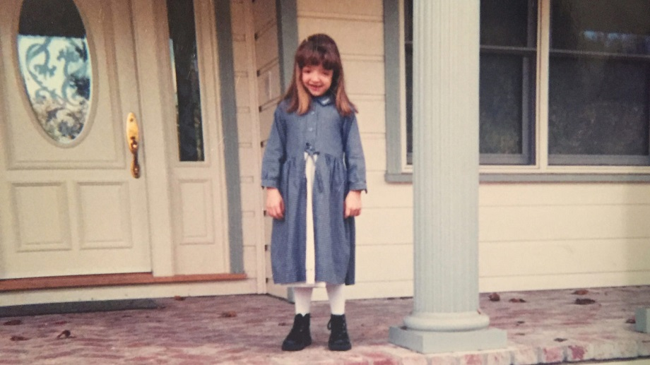 A young girl with Crouzon syndrome wearing a long blue coat stands in front of a white door.