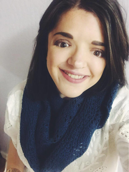 A young woman with dark hair wearing a blue scarf and white top smiles at the camera.