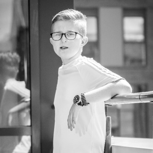 A black and white photo of Sam, who has a cleft lip and palate - he's leaning against a railing