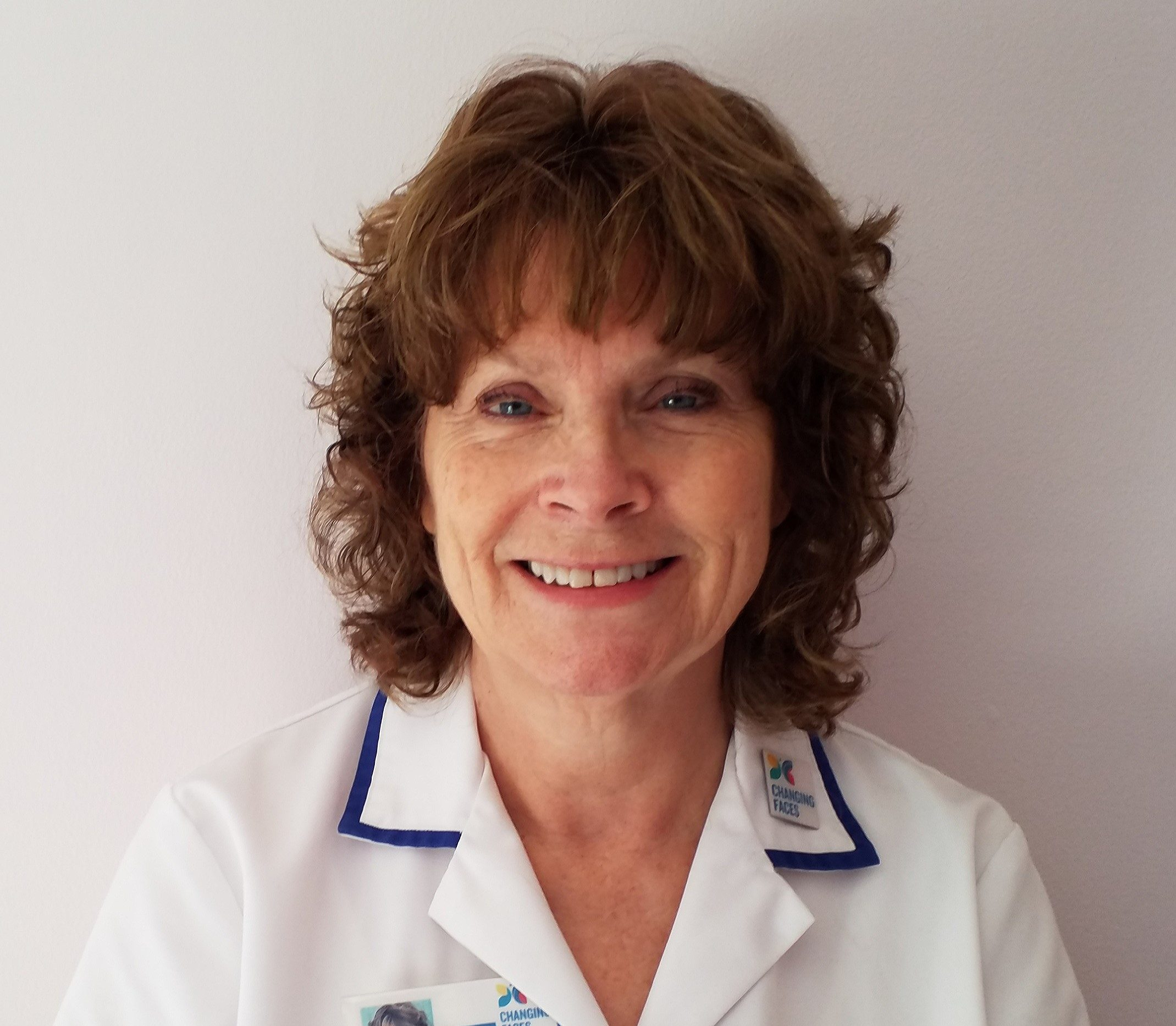 A skin camouflage practitioner wearing a white medical coat with a Changing Faces badge, smiles at the camera. She has short curly hair.