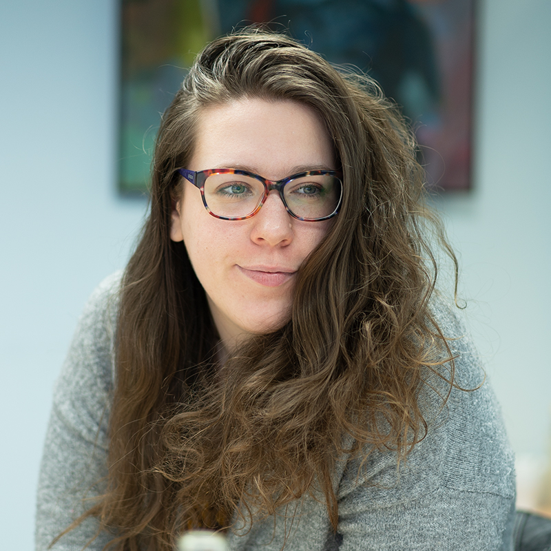 A young woman with curly brown hair, wearing glasses and a grey cardigan, looks to the right of the camera, slightly smiling.