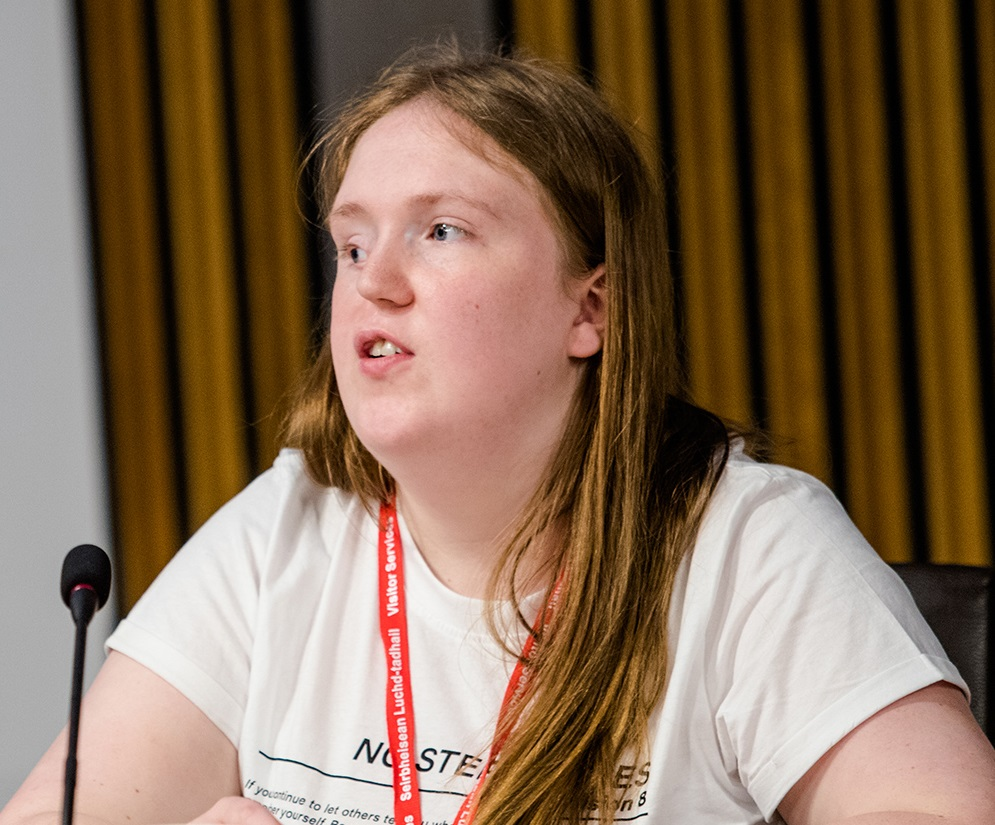 A teenage girl who has a facial cleft sits at a desk in front of a microphone. She has long hair and is speaking towards the left of the camera.