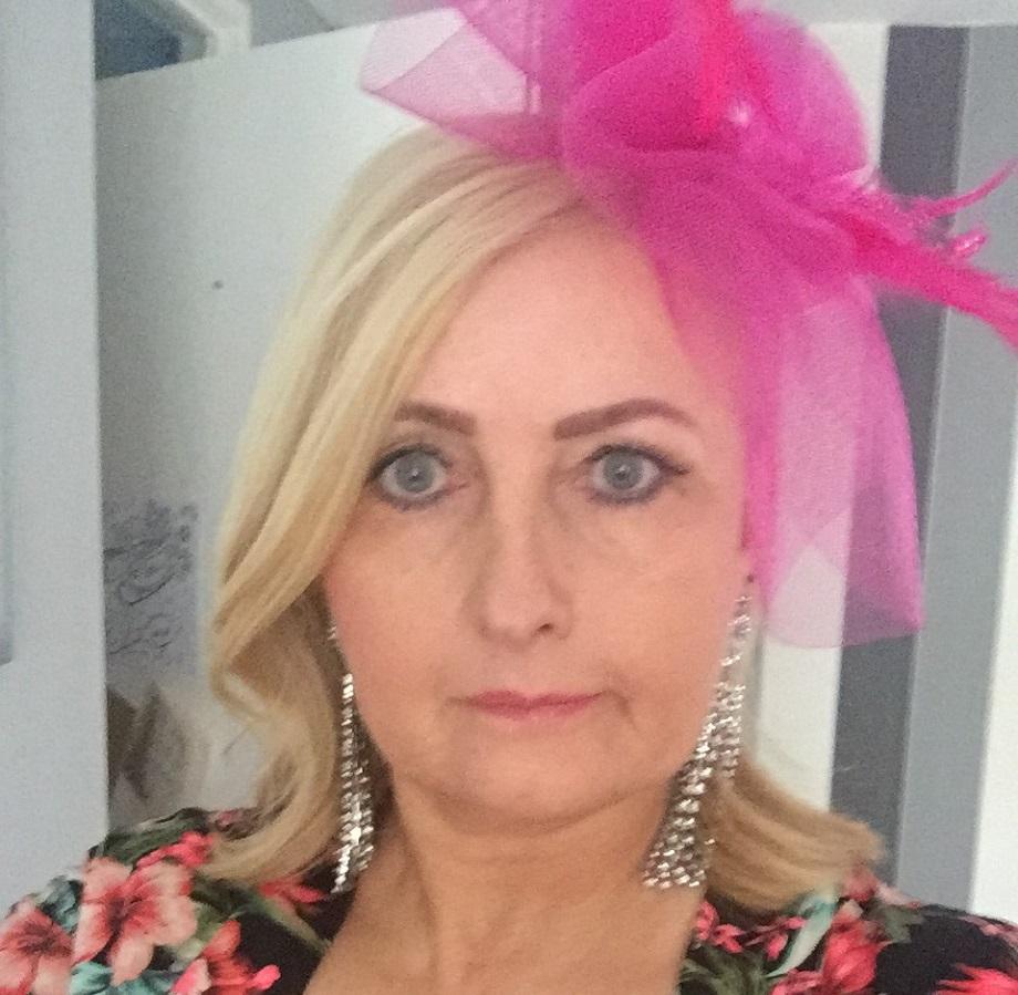 A woman wears a pink fascinator.