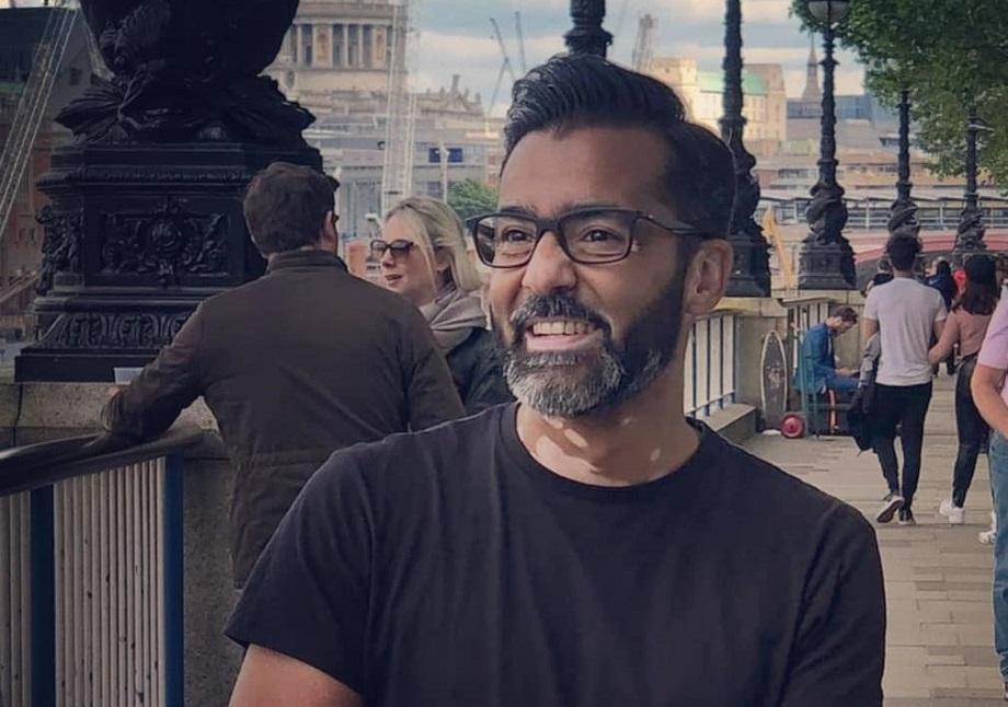 A man with a grey beard and vitiligo on his neck, smiles on London's Southbank.