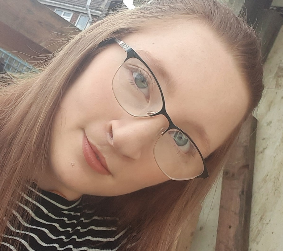 A teenage girl, who has a cleft lip and palate, wears glasses and a striped top.