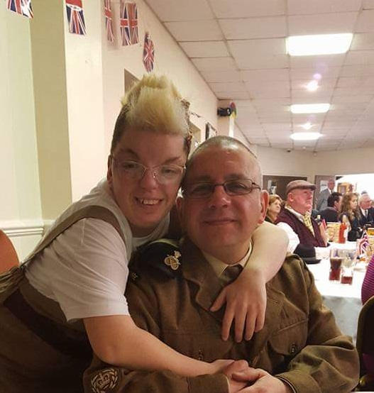 A young woman hugs a man wearing military uniform. They both smile at the camera.