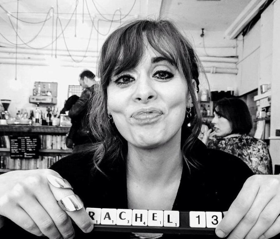"A woman holds up Scrabble tiles reading ""Rachel""."