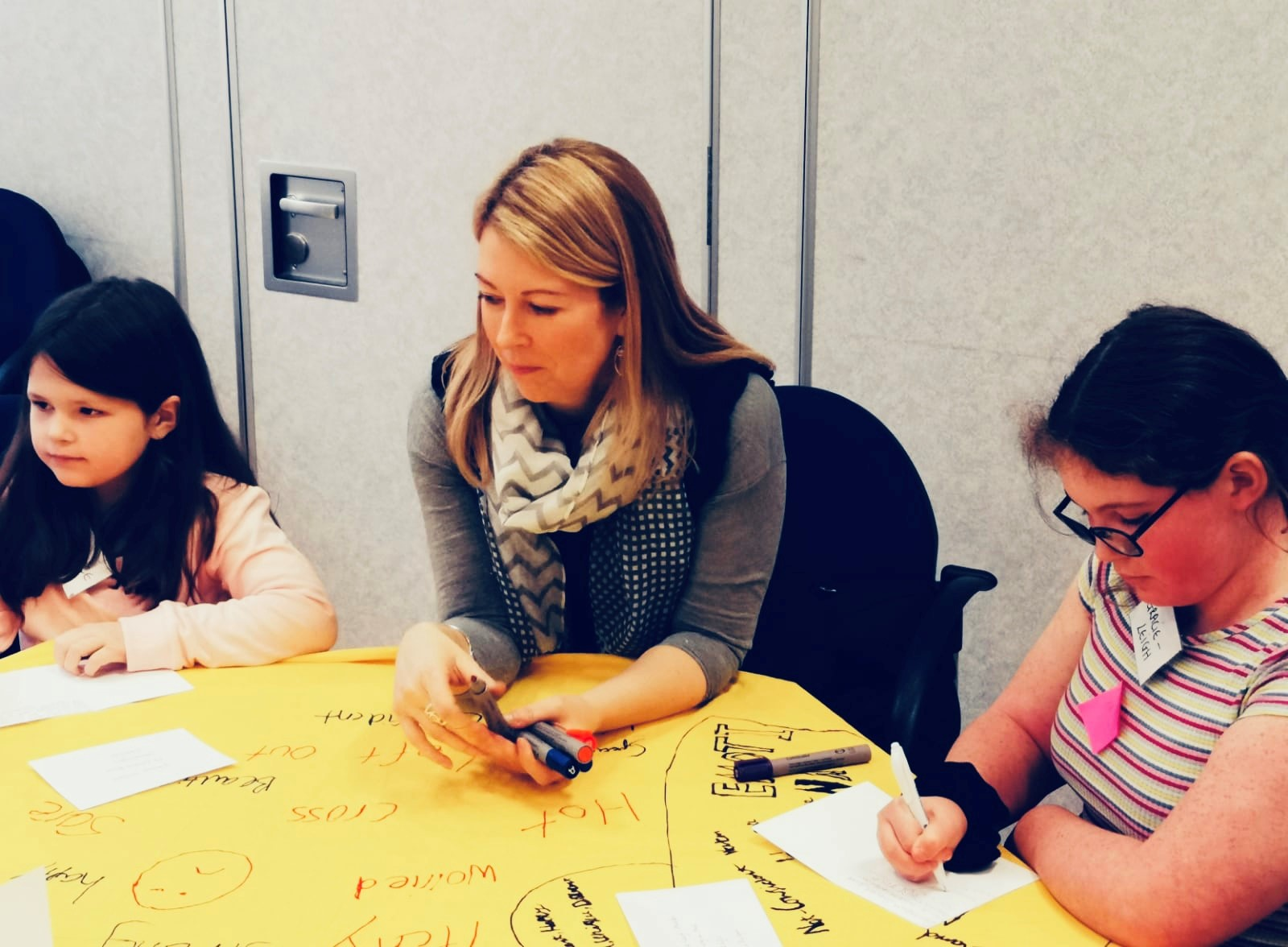 A woman sits at a table with two young girls either side of her. They are drawing on yellow paper.