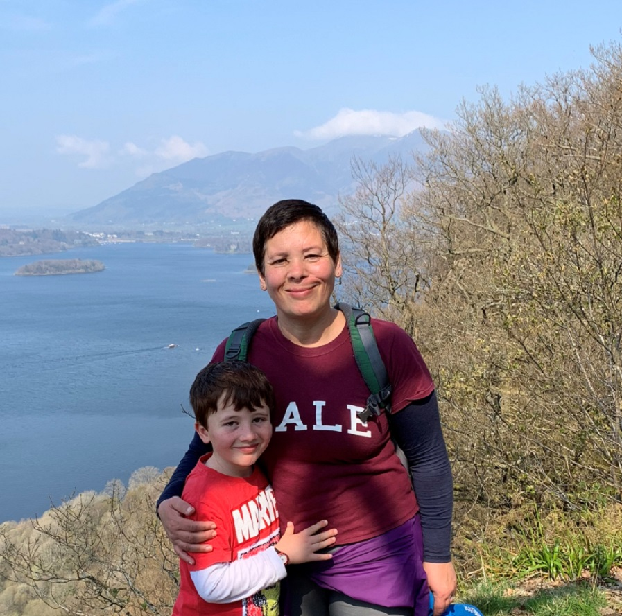 A woman and little boy pose together in front of a beautiful lake and mountain landscape.