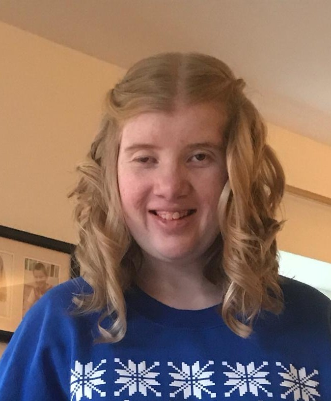 A young girl with ptosis wears a blue and white top and smiles at the camera. She has blonde curly hair.