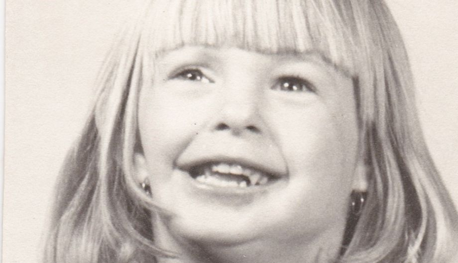 A young girl, 4 to 6 years old, with long blond hair, smiling
