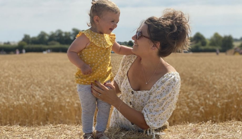 A woman wearing a white floral blouse and sunglasses. She is holding her daughter who's wearing a yellow top and white leggings. She is smiling at her mother. A field of straw is in the background.
