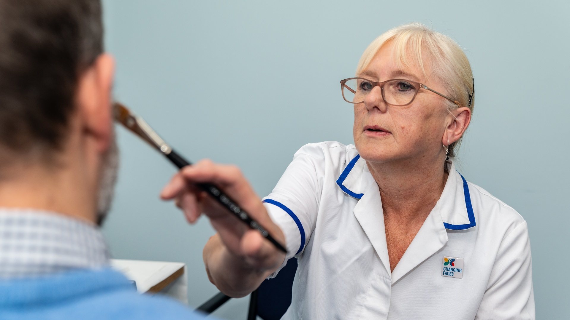 A woman in a nurse's top, wearing glasses with white hair tied up, applies skin camouflage products to a man's face. We can see the back of the man's head only - he has some stubble on his face and wears a shirt and a blue jumper.