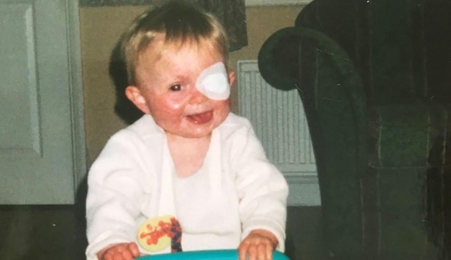 A toddler in a white cardigan with short blond hair and a eye patch pushes a trolley of toys