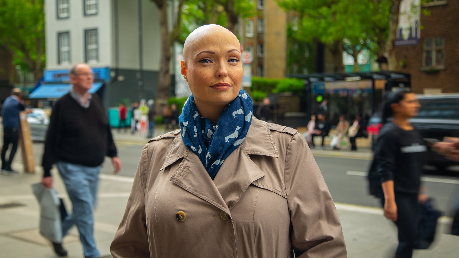 Brenda, who has alopecia, stands in a busy street wearing a beige coat and a blue scarf
