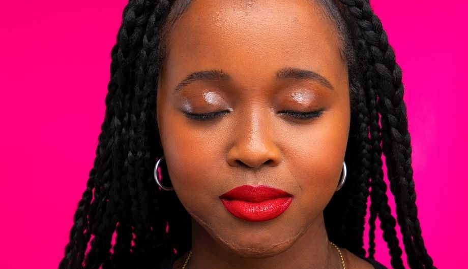 A young Black woman, 20s, she has her eyes closed and is wearing red lipstick and earrings. Behind her is a pink backdrop.