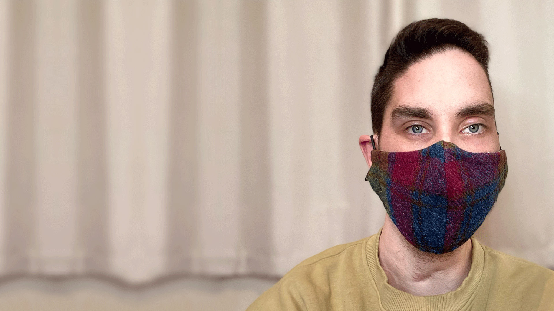 A man wearing a face mask looking directly to camera