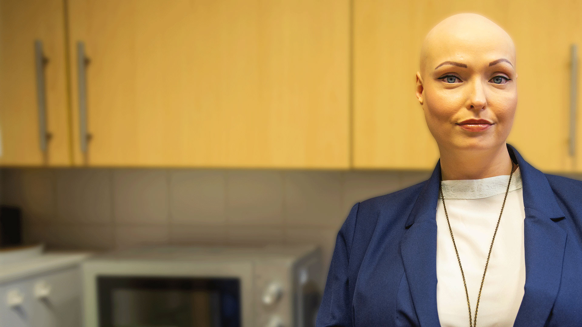 A woman with alopecia stands in the kitchen, gazing at the camera