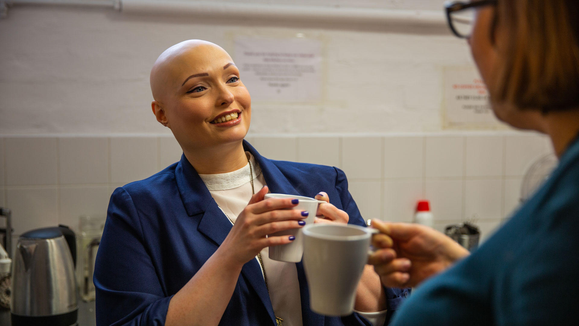 A woman smiles as she speaks with a colleague on their tea break
