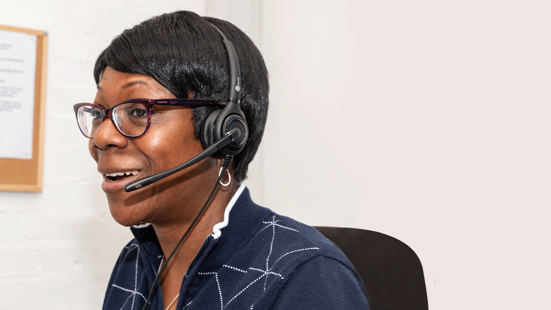 Dola sitting in an office, wearing a headset and smiling