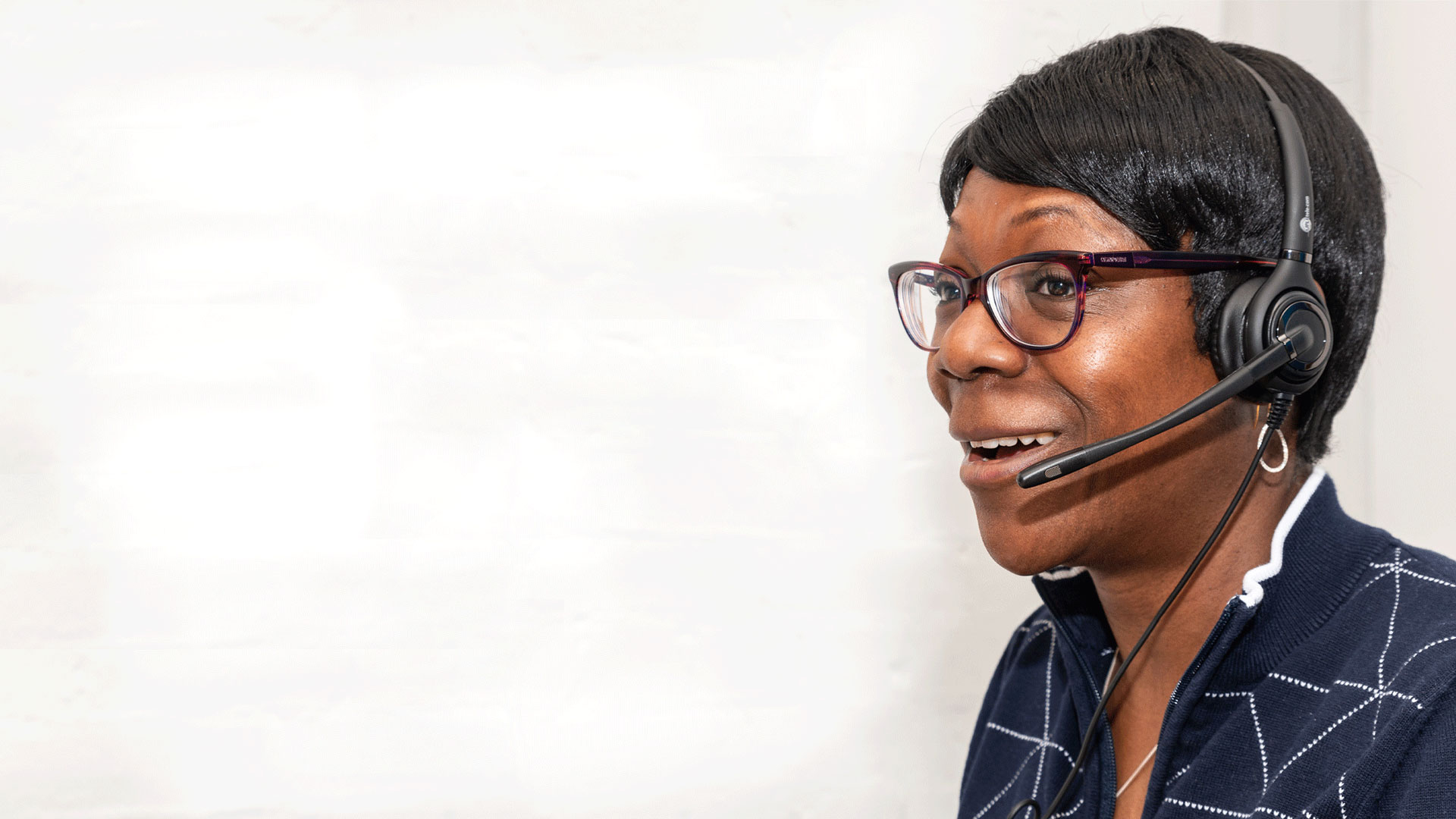 Helpline operative in profile, wearing headset and smiling