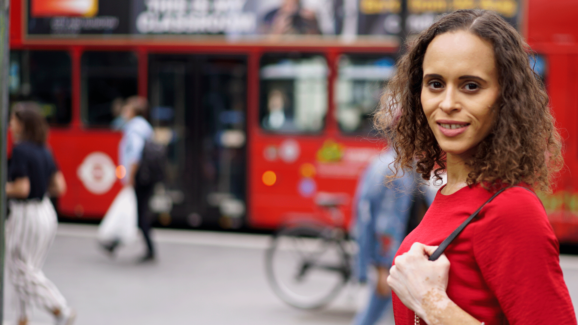 Natalie outside, smiling and looking confidently to camera, with a London bus in the background