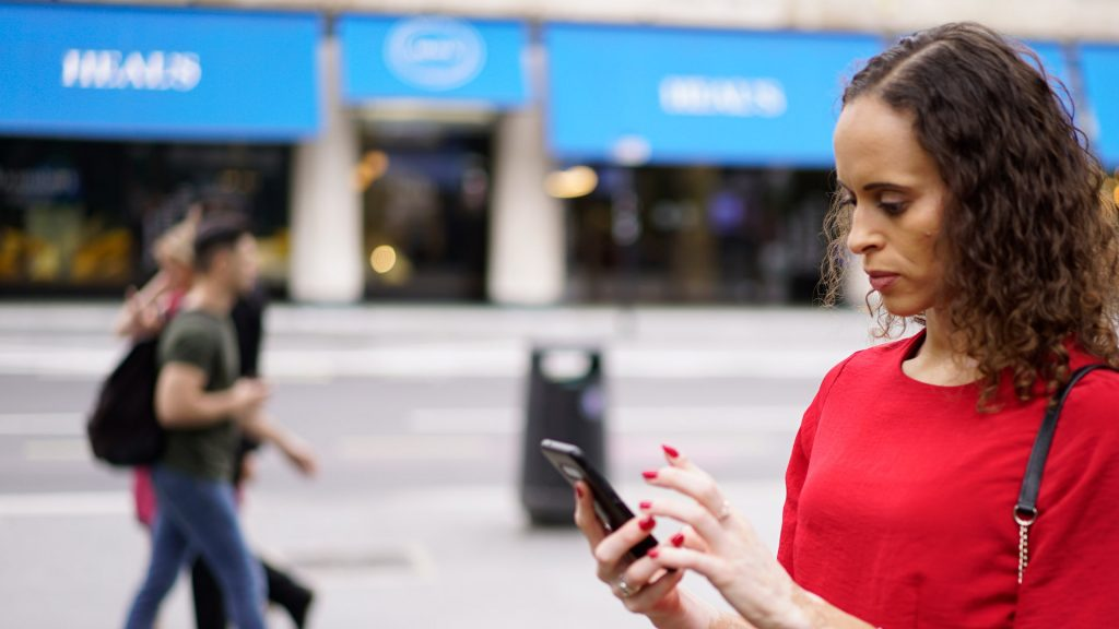 Natalie using a smartphone on the street, with passers-by and shops in the background