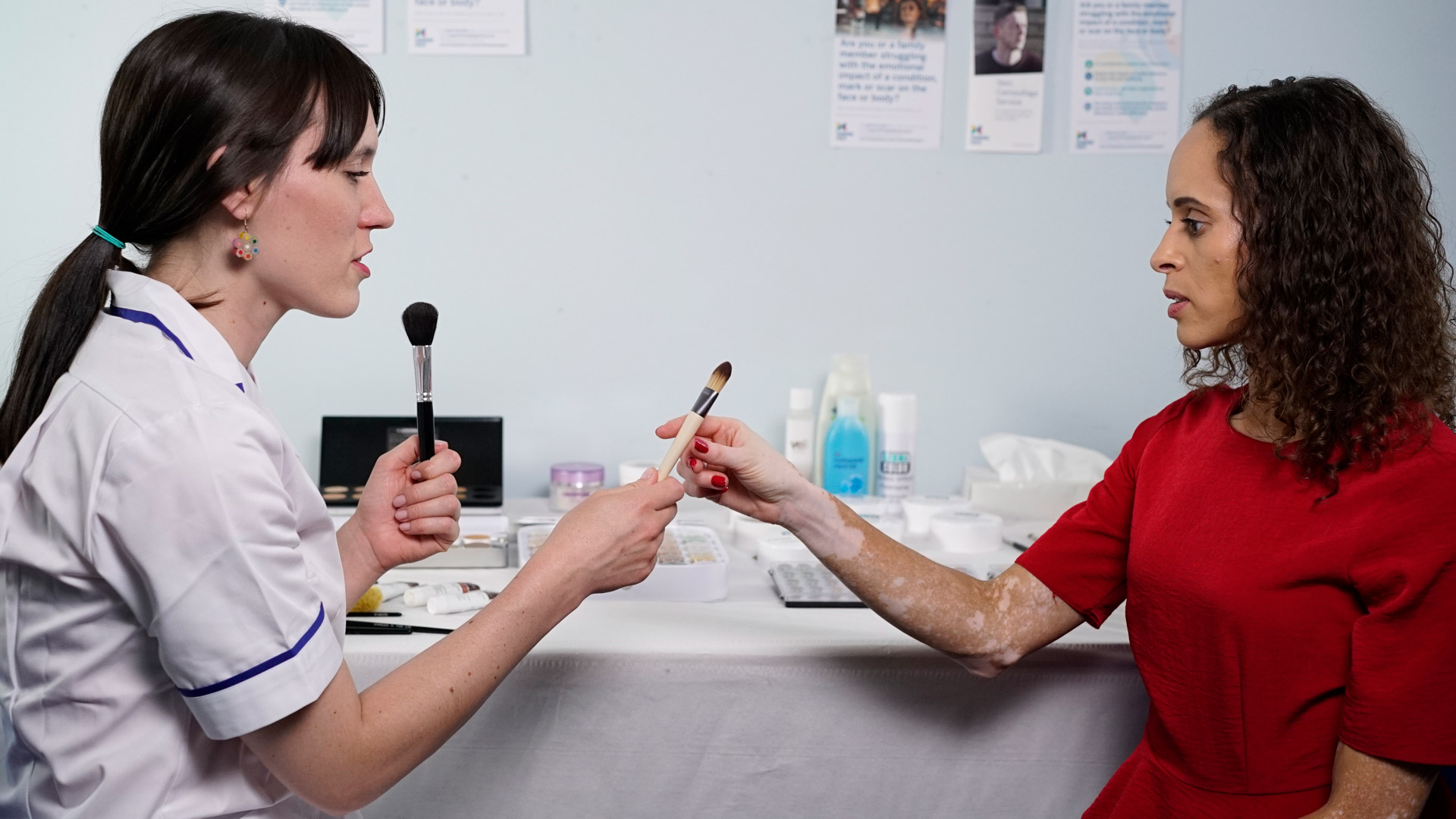 A Skin Camouflage Service client takes a brush from a practitioner