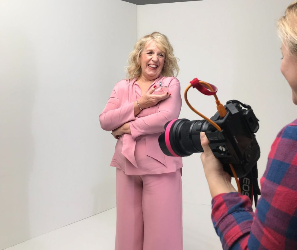 Paulette in a pink suit, smiling on an Avon photo shoot