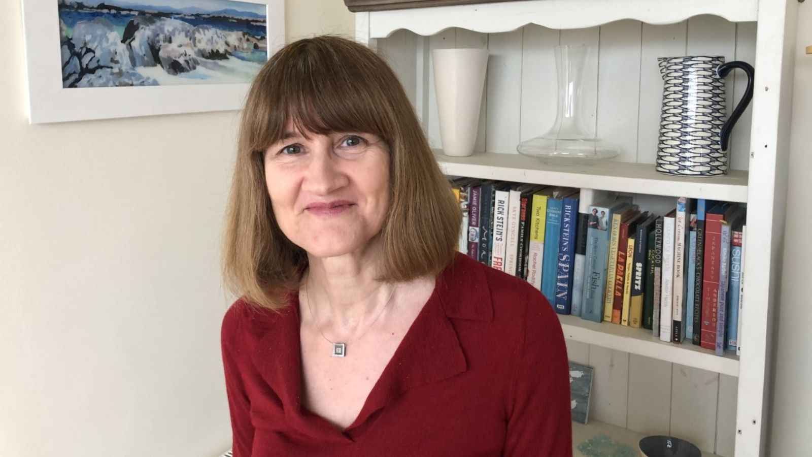 Heather Blake, a woman with shoulder length brown hair, wearing a red blouse, standing in front of a bookcase, filled with books and ceramics.