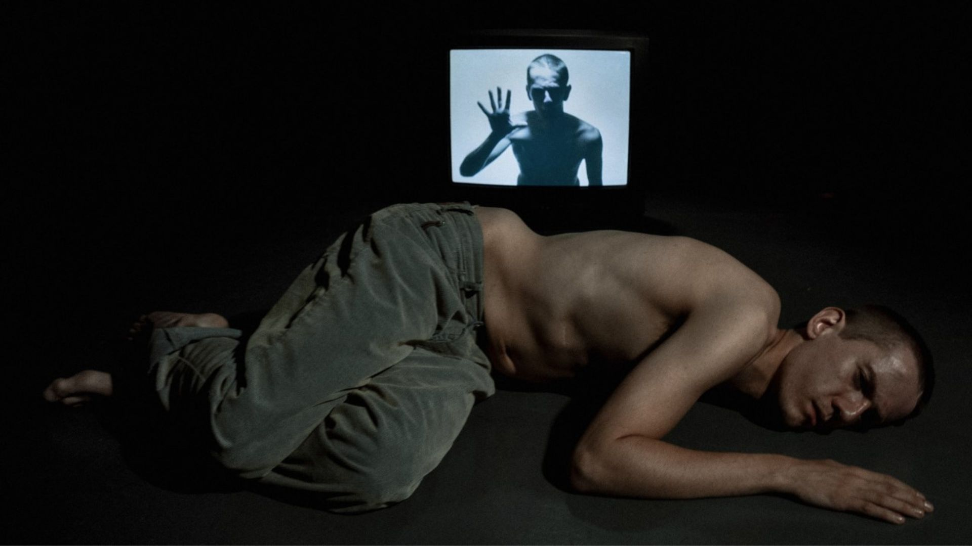 Robert, a young man in his 20s, topless wearing green trousers, lying on the ground. Behind him is a tv with an image of himself on the screen.