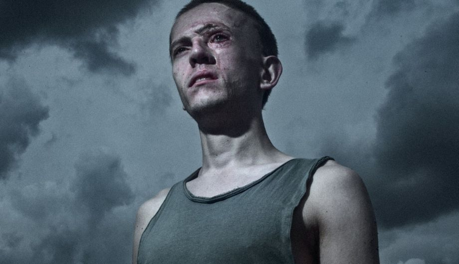 Robert, a young man in his 20s with facial scars, wearing a grey singlet, pictured against a dark sky.