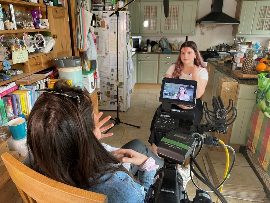 Sophie sitting in a kitchen, facing the camera, chatting to a woman with video equipment facing away from the camera