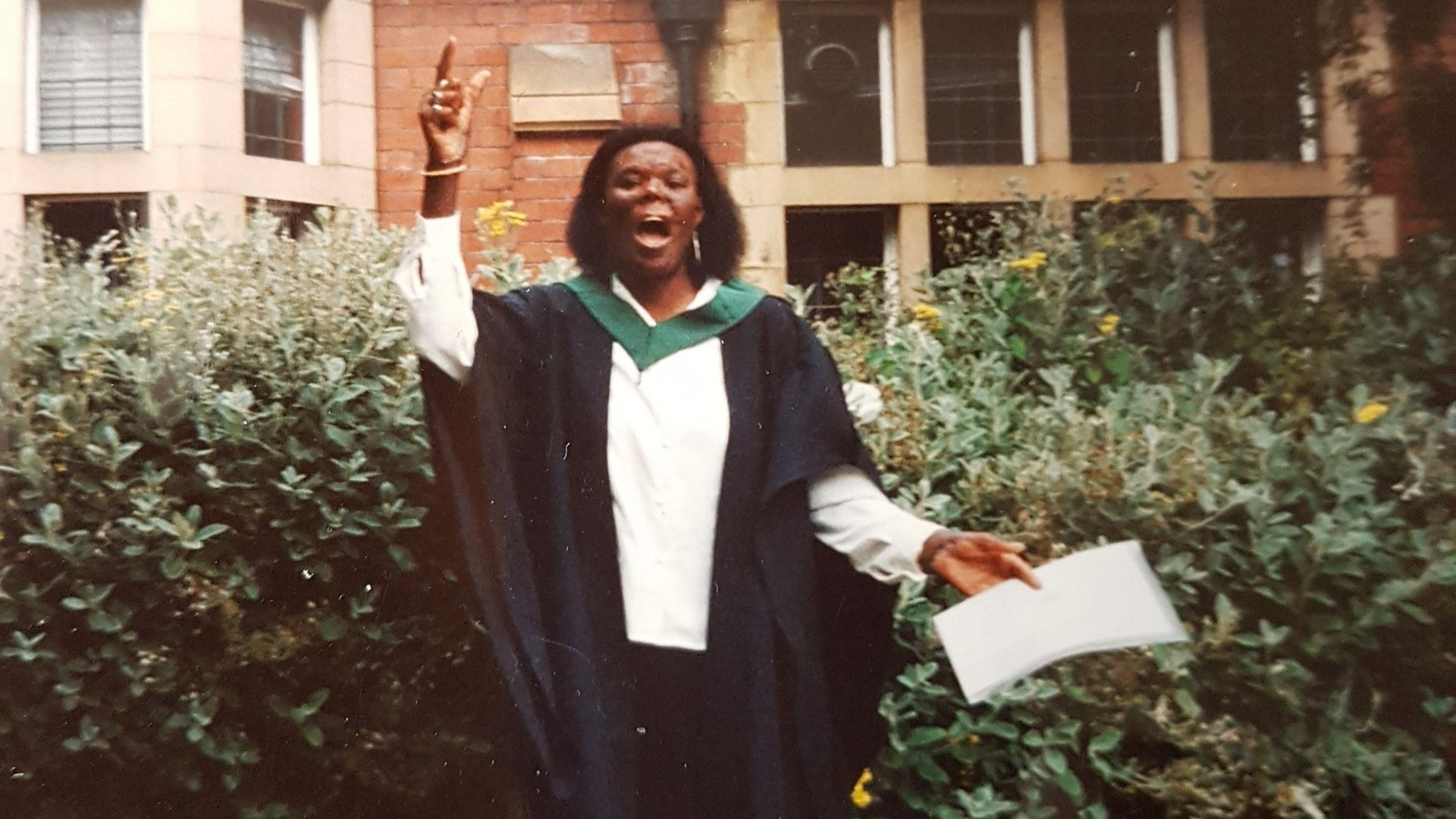 A woman, early 20s, in her graduation robes. She is holding a certificate in one hand and pointing in the air with her other other hand. She is excitedly shouting. Behind her is a bush and a building.