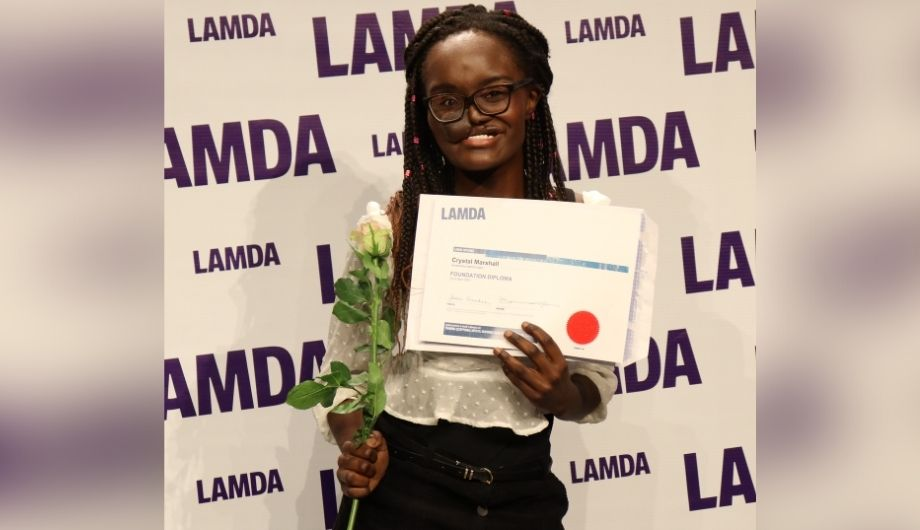 Crystal, a women in her early 20s with a skin flap. She's wearing a white blouse and black trousers and holding a rose and a graduation certificate from LAMDA. Behind her is a wall covered all over with the word 'LAMDA'