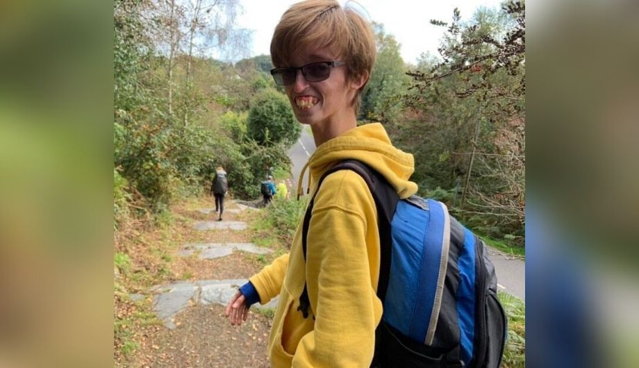 Dylan, a teenager, wearing a yellow hoodie and a blue backpack. He's outside walking down a forest path and has turned his head to smile at the camera.