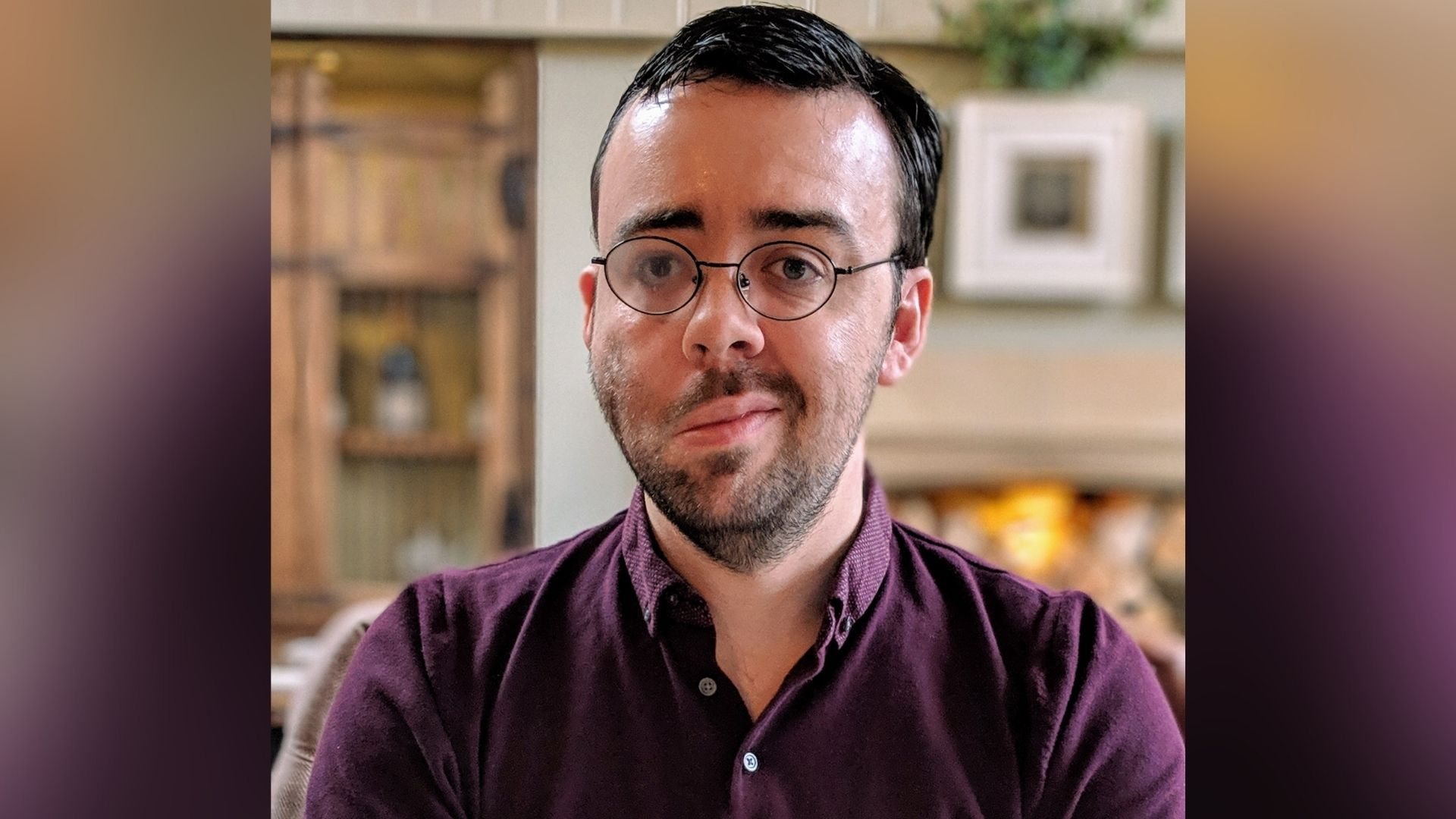Kevin, a man, 30s, with short dark brown hair, stubble and glasses. The right side of his face droops due to loss of muscle control. He's wearing a purple shirt.
