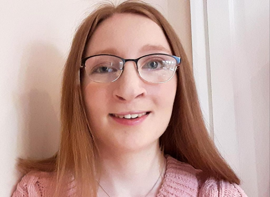 A teenage girl with long brown hair and glasses, who has a cleft lip and palate