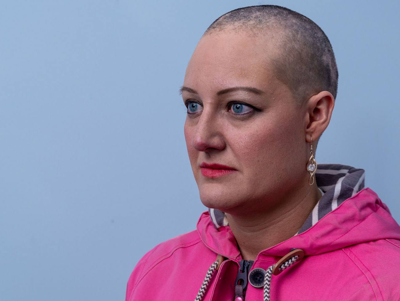 Julie, who has alopecia, against a blue background, looking off camera