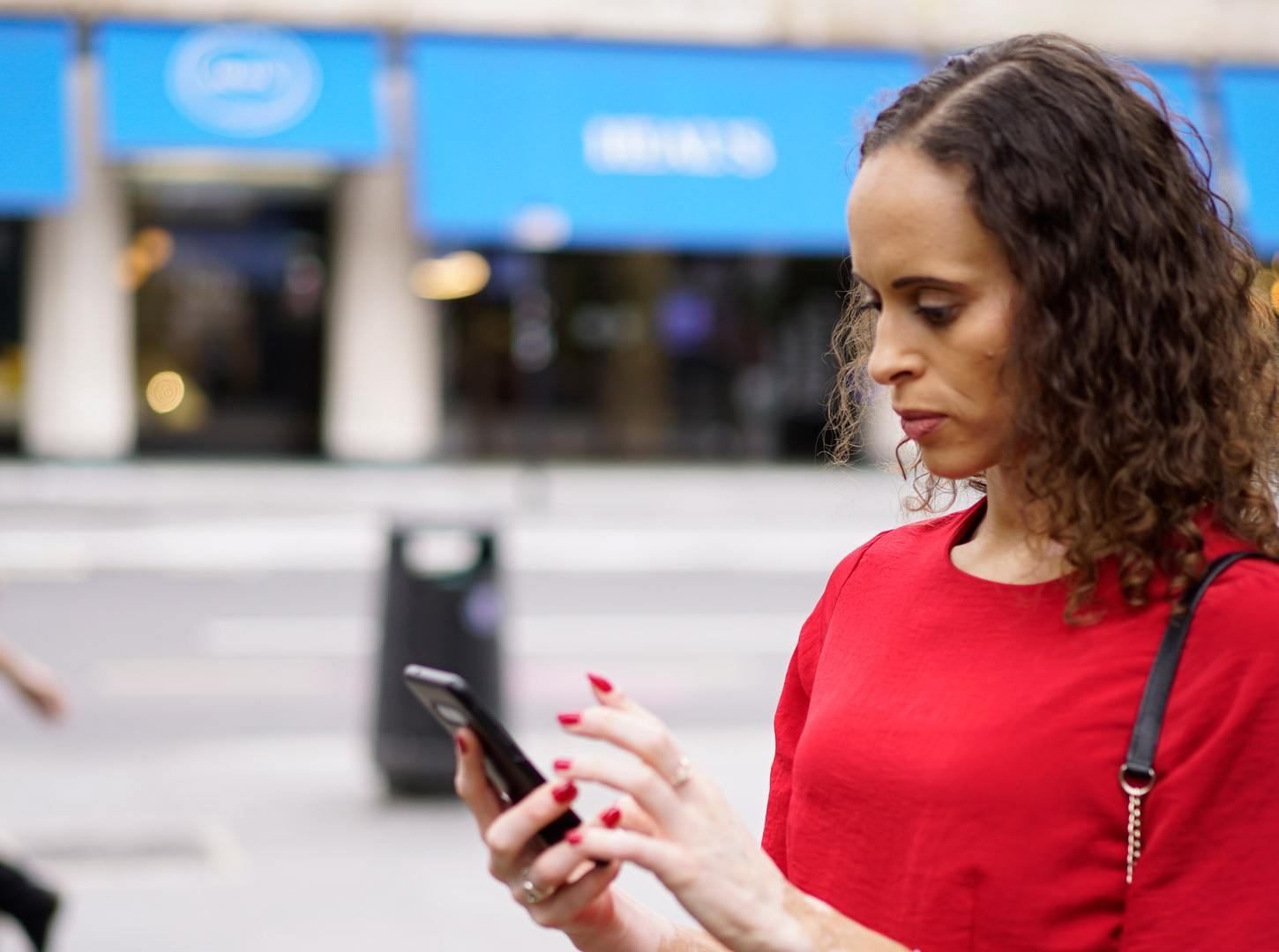 A woman with wavy, shoulder-length hair in a red top using a smartphone on the street.