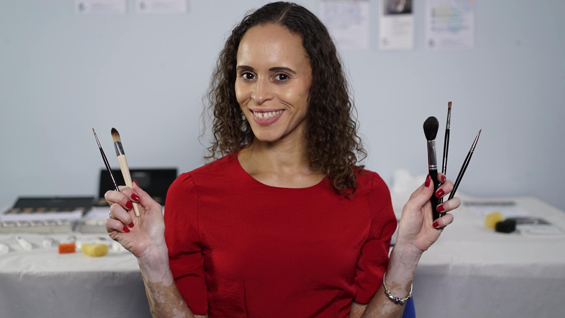 A woman in a red top with vitiligo on her arms holding up skin camouflage brushes and smiling at the camera